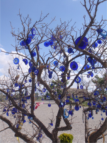 A bare-branched tree with dozens of blue nazar, whole and broken alike
