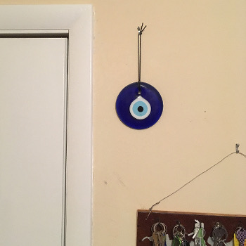 Glass blue evil-eye icon, by door with rack of keys below