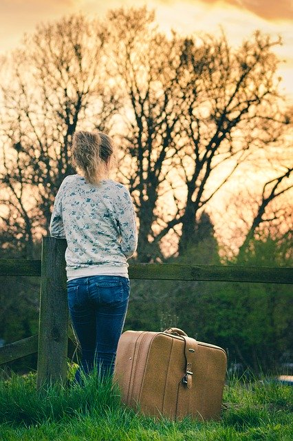 Person standing next to suitcase, looking out over field and trees at dusk