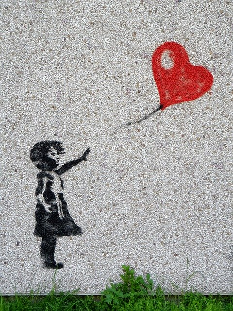 street art of girl releasing balloon