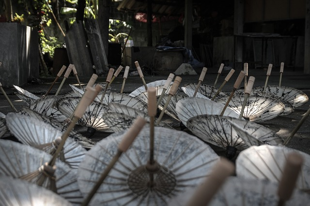 photograph of about a dozen upside down parasols on the ground