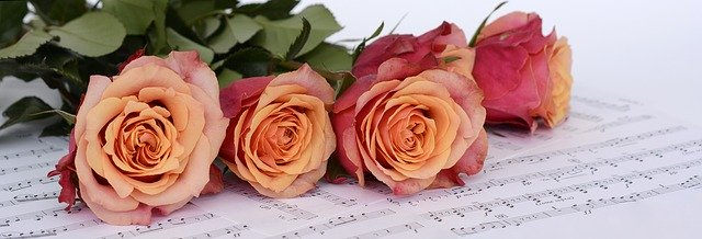 Orange/pink roses on top of a sheet of music